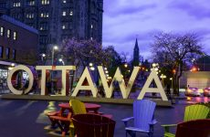 Tourists are taking pictures with the Ottawa sign installed at Inspiration Village. It's known for its colorful street art and trendy stores in Ottawa,Canada.